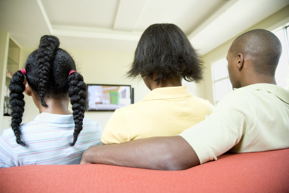 A family is seated on their living room sofa and watching TV together, with their backs to the camera. Horizontally framed shot.