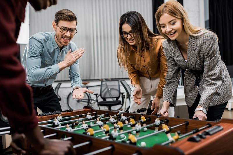 Young people playing table football in office.