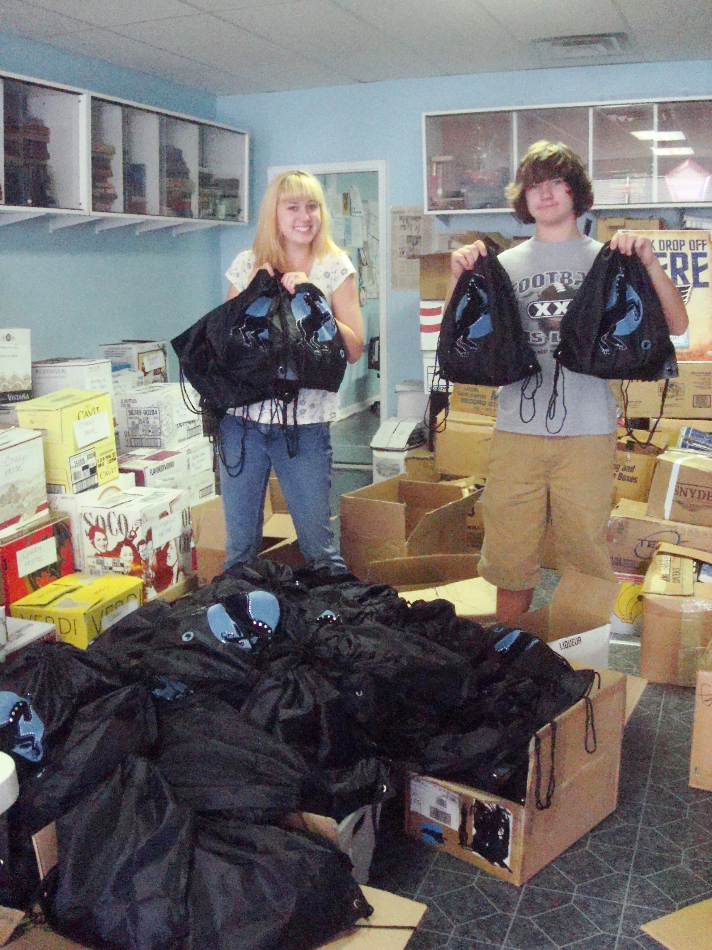 "Ashley and Matt McNeill show off a few of the finish ""swag bags."" Hundreds were assembled for Toys for Tots."