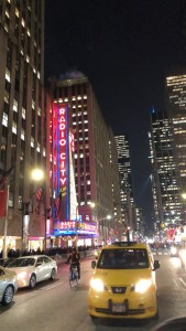 Radio City Music Hall in NYC lit up at night.