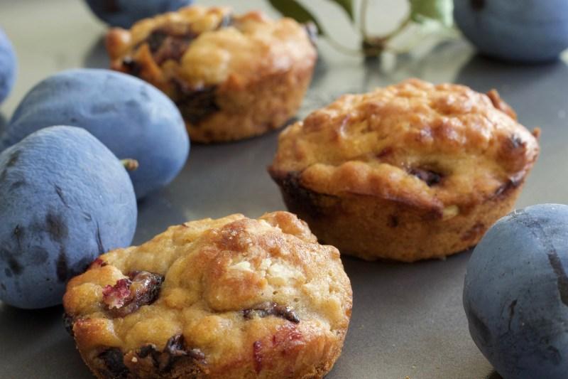 Baked vegan plum muffins laying on a baking sheet.