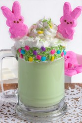 Green milkshake in a glass with whipped cream and marshmallow peeps.