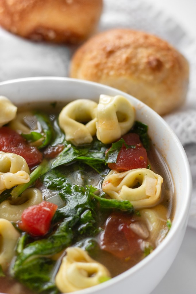 Tortellini Soup in a white bowl with garlic knots.