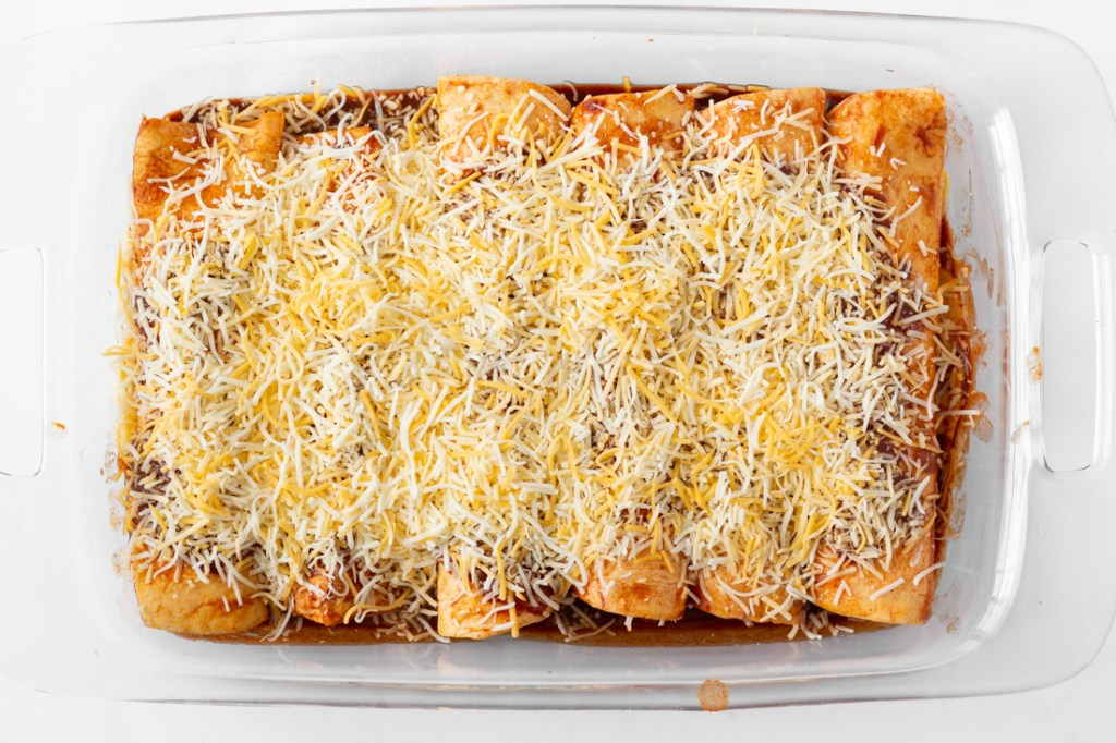 Sprinkled cheese on enchiladas.
