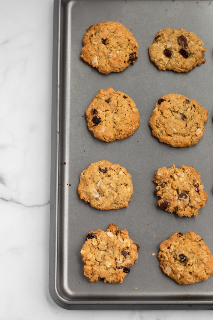 Baked coconut oat cookies on a tray.