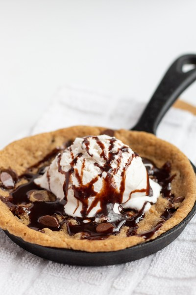 Chocolate Chip skillet cookie topped with ice cream and chocolate syrup.