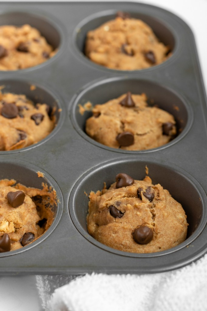 Peanut Butter Chocolate Chip Muffins in a muffin tin.