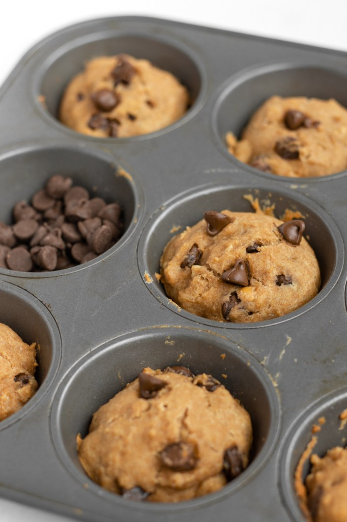 Chocolate Chips and muffins in a muffin tin.