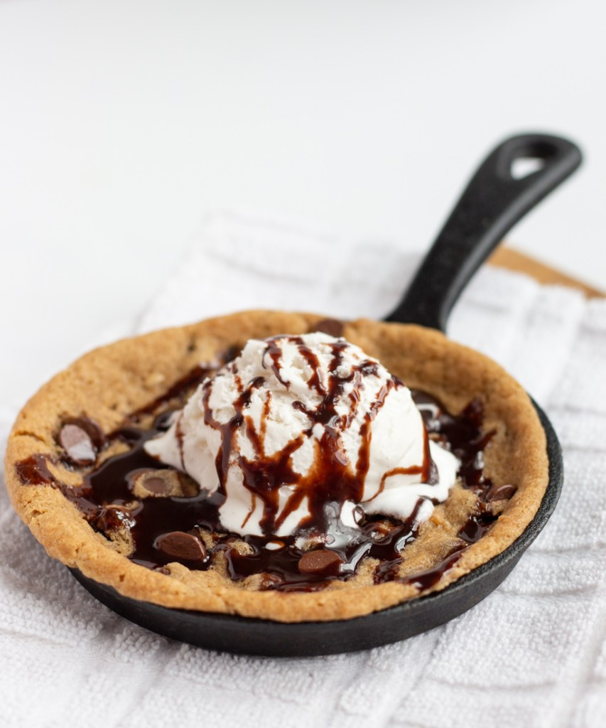 Skillet cookie topped with a scoop of vanilla ice cream and chocolate drizzle.