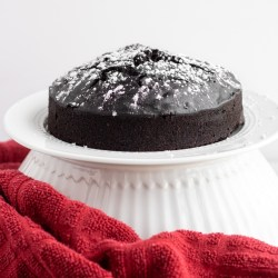 Instant Pot Chocolate Cake on white cake stand with red towel.