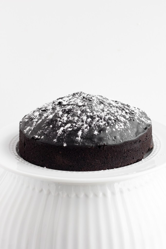 Instant Pot Chocolate Cake on white cake stand.
