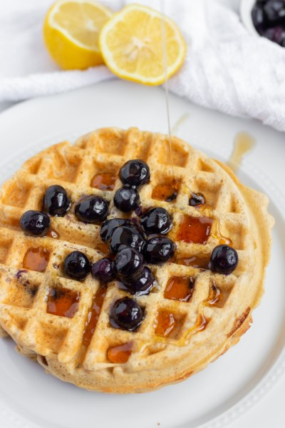 Blueberry waffles drizzled with maple syrup.