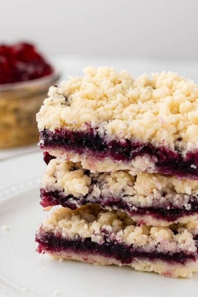Stacked cherry crumble bars on a white plate.