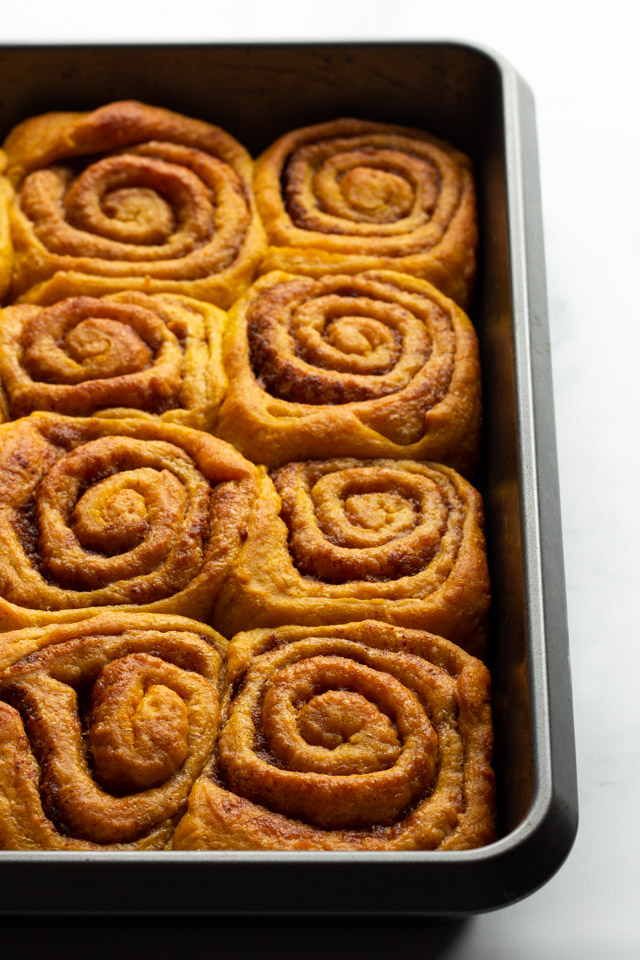 Pumpkin cinnamon rolls in a metal baking tray.