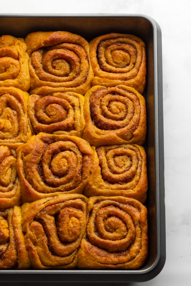 Pumpkin cinnamon rolls in baking tray.