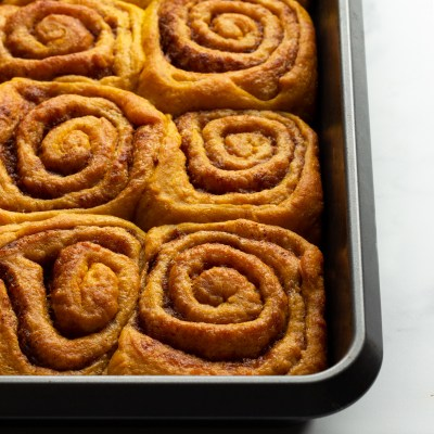 Pumpkin Spiced cinnamon rolls in a metal tray.