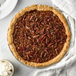 Pecan Pie with whipped cream and a white napkin.