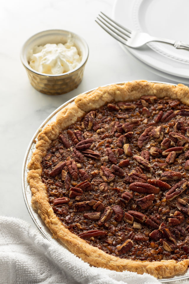 Pecan Pie with a cup of whipped cream.