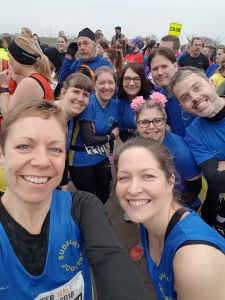 Emma Richbell, Jodie Budd, Charlotte Richardson, Julie Rout, Rachel Miles, Zoey Battell, Steve Roberts and Brian Bloomfield at the Colchester Half Marathon 2018 start line.
