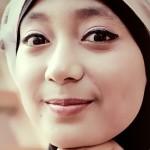 A woman wearing a hijab smiling at the camera.