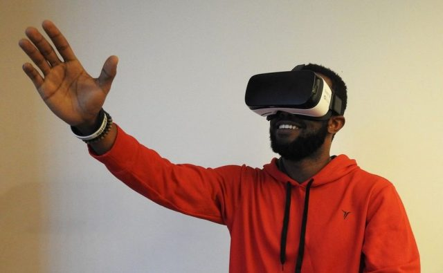 an African American man wearing a VR headset stands in front of a light coloured wall, reaching into the air with his right hand