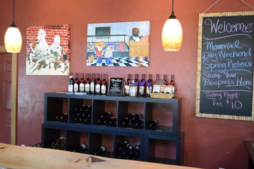 Sue Clancy's fine art on exhibit above some very fine wines at Burnt Bridge Cellars