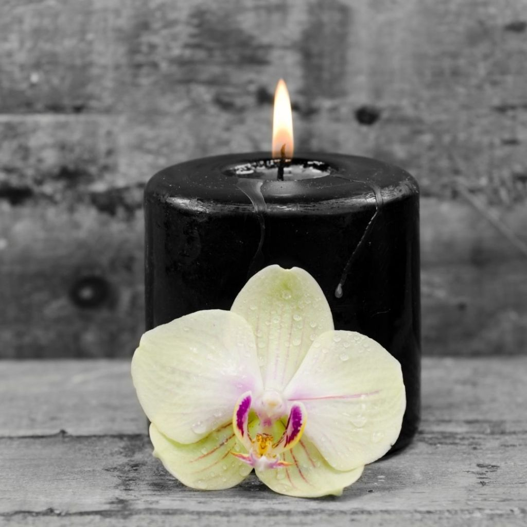 Black candle with orchid