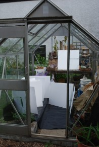 panels painted with gesso drying in greenhouse