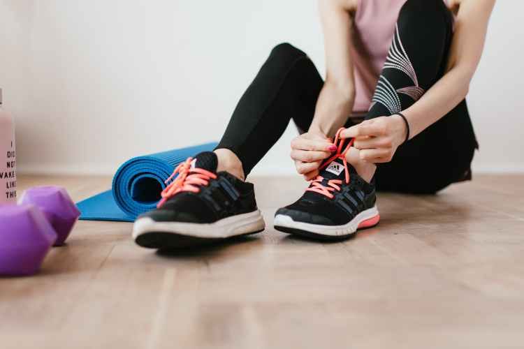 anonymous slender female athlete tying shoelaces near sport accessories