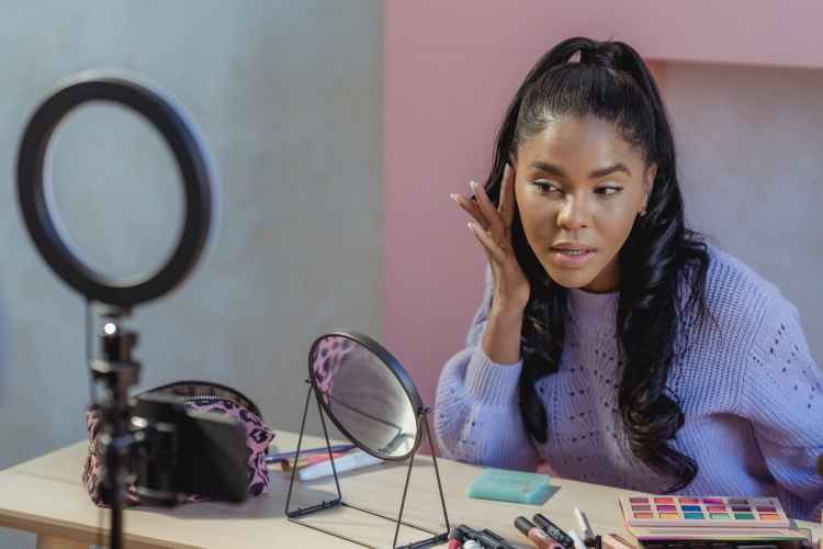 focused black blogger applying makeup and recording video