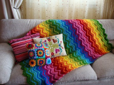 a rainbow ripple afghan - how pretty! Love the pillows too