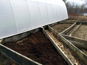 A triangular bed with soil ready to receive plants
