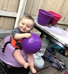 Noah Tomlin holding a ball while sitting in a Bumbo baby seat
