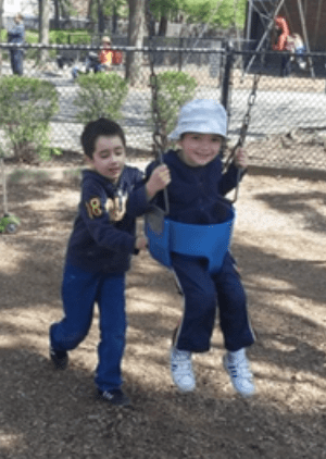 Anthony Valva pushing his brother Thomas on a swing