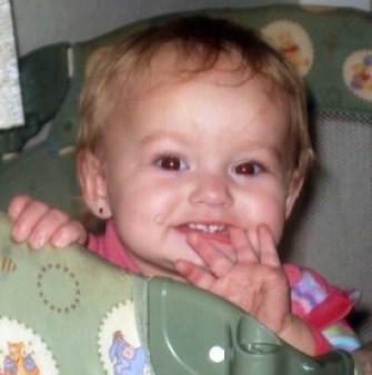 Alissa Guernsey smiling in her playpen