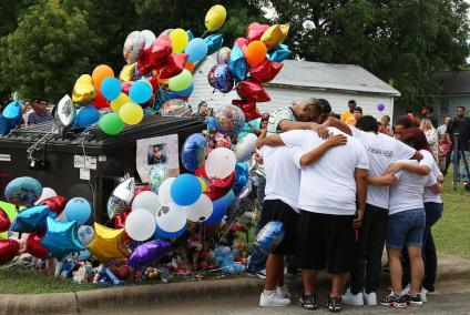Family members of Frankie Gonzales gather at the memorial surrounding the dumpster where his body was found