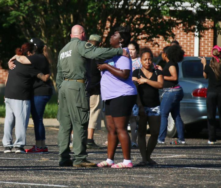SWAT officers comfort bystanders after news breaks that a body had been found in the search for Frankie Gonzales