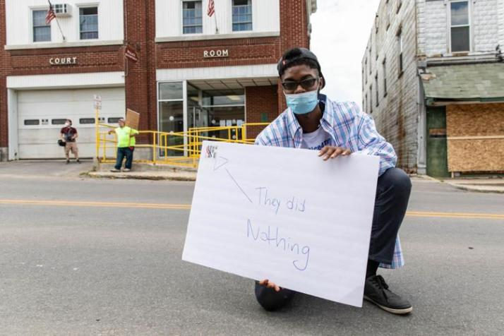 "Isiah Samuels holds a sign saying ""They did nothing"" in front of the Gouverneur Police Station"