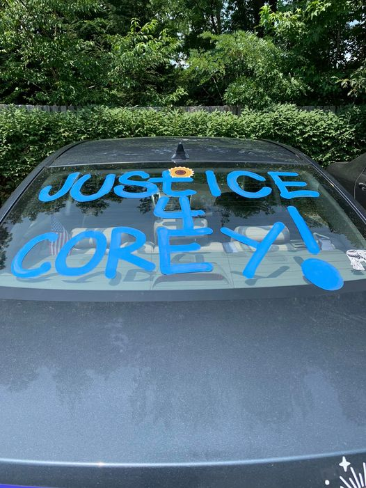 Car window reading Justice for Corey