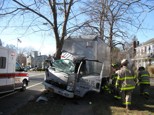 SOUTHOLD FIRE DEPARTMENT COURTESY PHOTO | Firefighters survey the scene where a delivery truck smashed into a tree in Southold Saturday morning.