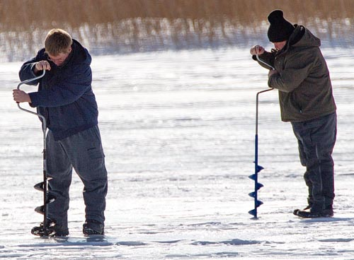 Two ice fishermen hard at work, drilling holes in the ice atop Great Pond in Southold. (Credit: Garret Meade)