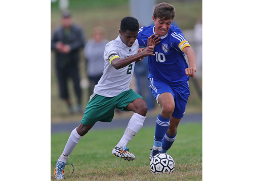 Bishop McGann-Mercy's Bereket Watts, left, and Mattituck's Paul Hayes cross paths during Tuesday's game, which saw 11 goals scored. (Credit: Garret Meade)