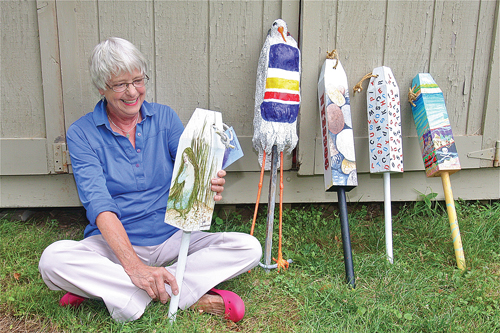 Artist Ann Sage of Greenport holds a buoy painted by artist Jada Rowland, her 'buoy bird' is next to her: the others are by Rich Feidler, John Wissemann and Nancy Wissemann Widrig. (Credit: Barbaraellen Koch)