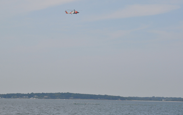 A U.S. Coast Guard helicopter searches between Robins Island and Nassau Point Monday afternoon. (Credit: Grant Parpan)