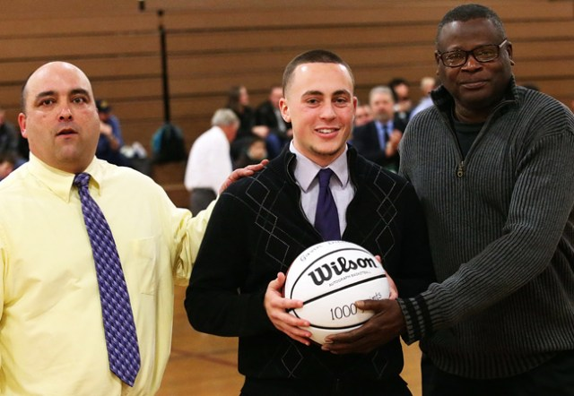 Greenport's Gavin Dibble, a freshman at the University of New Hampshire, was honored before Friday's game for scoring 1,000 career points. Varsity coach Ev Corwin (left) and former coach Al Edwards presented Dibble with a basketball. (Credit: Garret Meade)