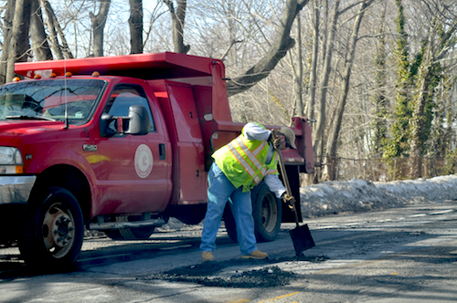 Southold highway department crews patching potholes on Main Street in Greenport in February 2014, when there wasn't as much work to do. (Credit: Cyndi Murray, file)