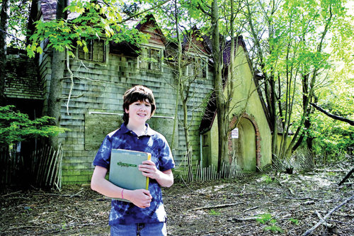 Ian Toy, at age 13 of Southold, in front of the house near Cedar Beach where Helen Keller may have spent the summer of 1936. (Credit: Suffolk Times, file)