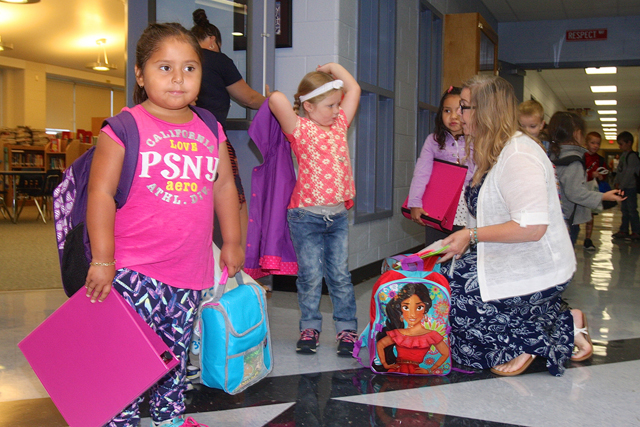 Kindergartner Maritza Fuentes-Olguin waits as her teacher Karen Krukowski talks with other students.