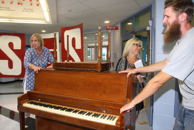 Orchestra teacher Audrey Grathwohl (left), band director Rene Suprina (center) and custodian Drew Averette move a piano to the music room on the first morning of classes.