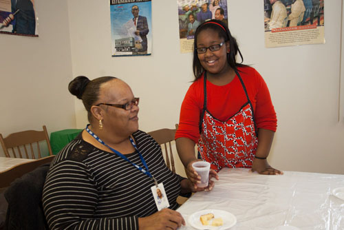 Jalisa Dixon, 11, serving  her mother, Janis Moore, dessert.